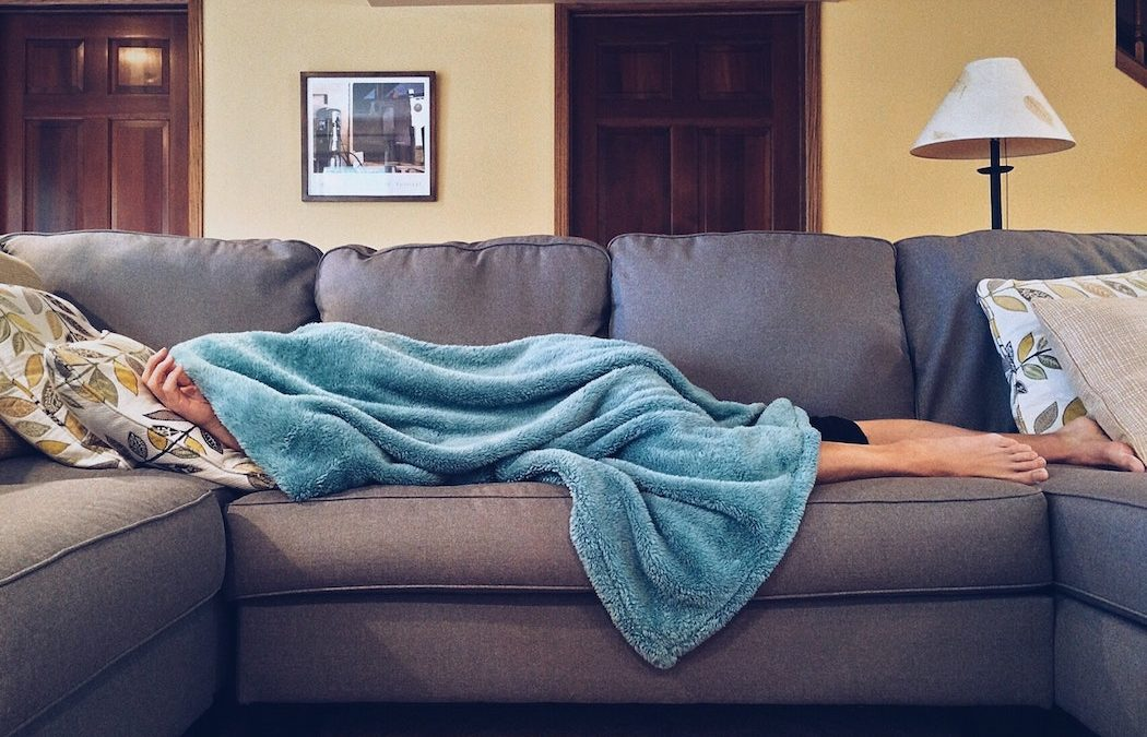 cold and flu season person laying on couch covered in blue blanket in living room