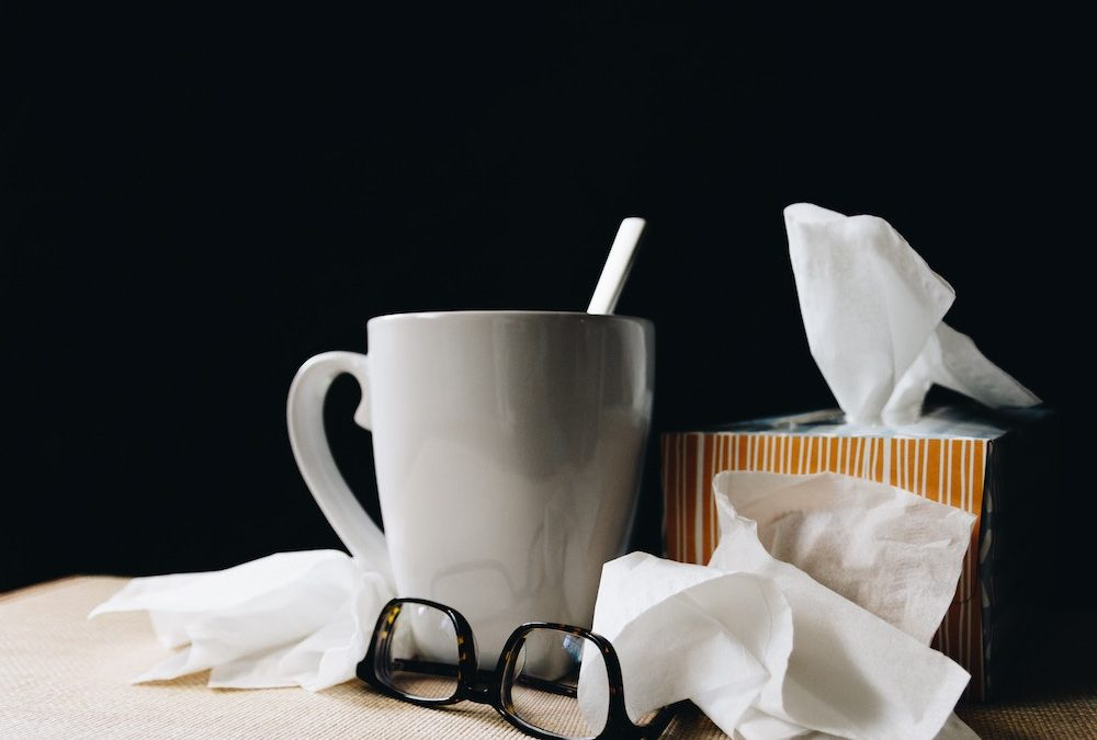 health hazards mug with tissues and glasses on tabletop with black background